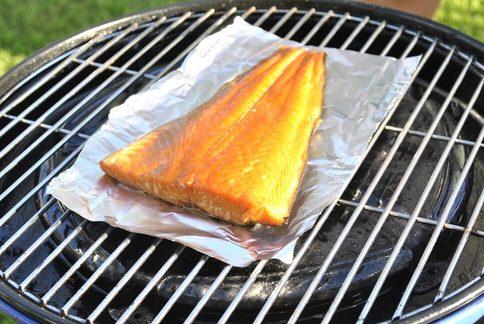Halve warm gerookte zalm op aluminium folie op de barbecue bbq