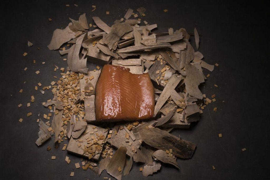 Een half stuk warm gerookte zalm op houtsnippers die net uit de rookton komt.